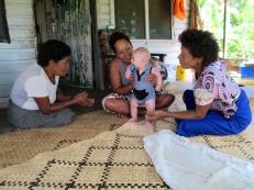 Pauline cuddling Max with mother Elizabeth at Yanuca village
